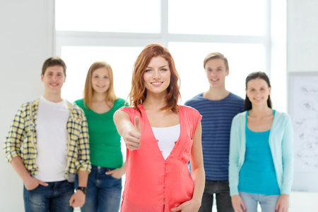 people looking up: education and school concept - group of smiling students with teenage girl in front showing thumbs up