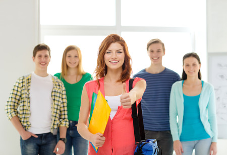 people looking up: education and school concept - group of smiling students with teenage girl in front with bag and folders showing thumbs up Stock Photo