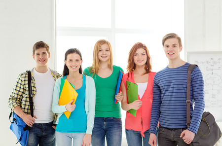 scholar: education and school concept - group of smiling students with bags and folders at school