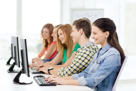 education, technology and school concept - smiling female student with classmates in computer class at school photo
