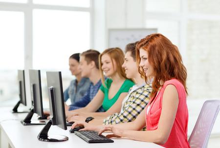 La educación, la tecnología y el concepto de la escuela - estudiante sonriente con sus compañeros en la clase de computación en la escuela Foto de archivo - 28897360