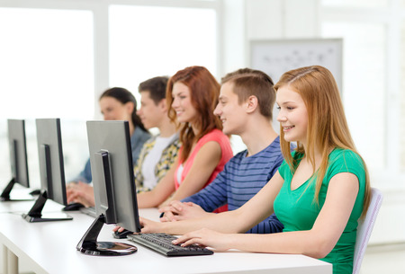 informatics: education, technology and school concept - smiling female student with classmates in computer class at school
