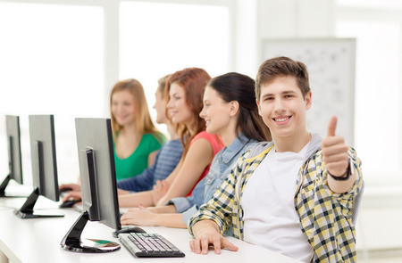 education, technology and school concept - smiling male student with classmates in computer class at school showing thumbs up photo