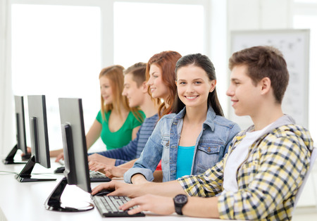 education, technology and internet - smiling female student with computer studying at school photo