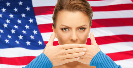 voiceless: usa politics, conspiracy and secrecy concept - woman with hands over mouth on american flag background