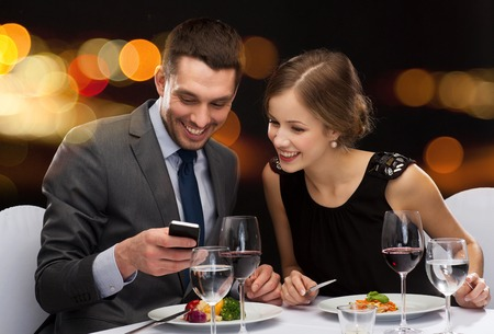 restaurant people: restaurant, technology, couple and holiday concept - smiling couple taking picture of main course with smartphone camera at restaurant
