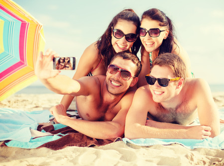 summer, holidays, vacation, technology and happiness concept - group of smiling people in sunglasses taking picture with smartphone on beach photo
