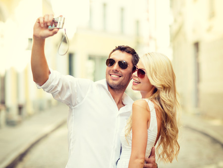 summer holidays, travel, vacation, tourism and dating concept - travelling couple taking photo picture with camera photo