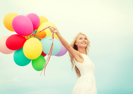 summer holidays, celebration and lifestyle concept - beautiful woman with colorful balloons outside photo