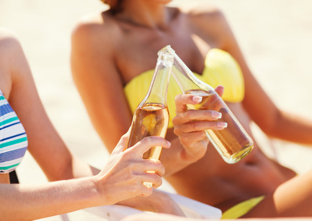 nonalcoholic beer: summer holidays and vacation - two girls in bikinis with drinks on the beach chairs Stock Photo