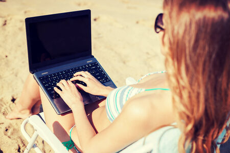 summer holidays, vacation, technology and internet - girl looking at laptop on the beach chair photo