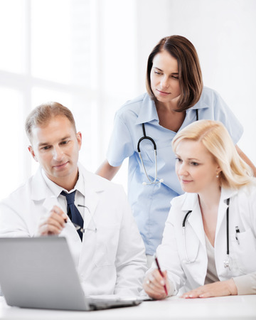 healthcare, medical and technology - group of doctors looking at laptop on meeting photo