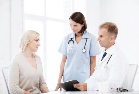 healthcare and medical concept - doctor and nurse with patient in hospital photo
