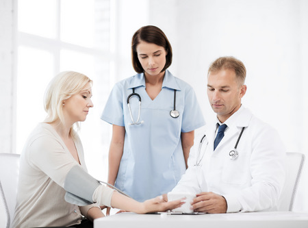 healthcare and medical concept - doctor and nurse with patient measuring blood pressure photo