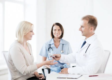 doctor giving pills: healthcare and medical concept - doctor giving tablets to patient in hospital