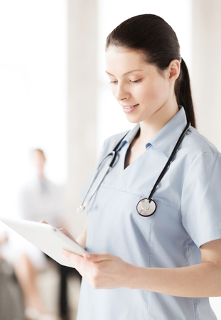 healthcare, medical and technology concept - female doctor with tablet pc photo