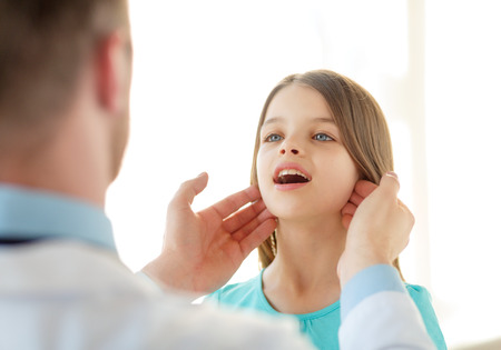 healthcare, child and medical concept - male doctor checks little girl lymph nodes in hospital