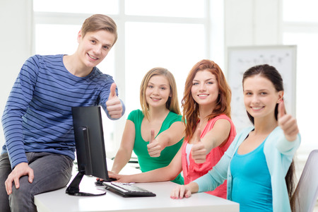education, technology, school and people concept - group of smiling students showing thumbs up in computer class at school photo