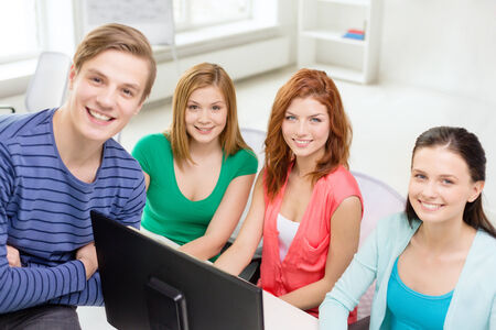 education, technology, school and people concept - group of smiling students having discussion in computer class at school photo