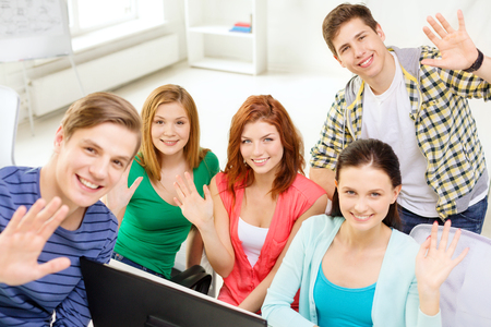 education, technology, school and people concept - group of smiling students waving hands in computer class at school photo