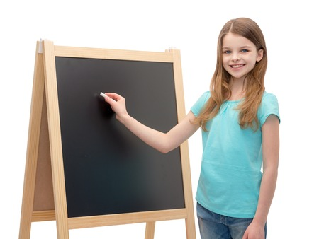 people, advertisement and education concept - happy little girl with blackboard and chalk photo