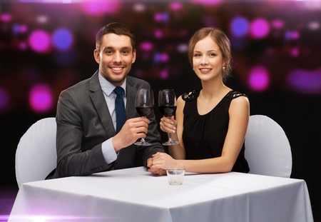restaurant, couple and holiday concept - smiling young couple with glasses of red wine looking at each other at restaurant photo