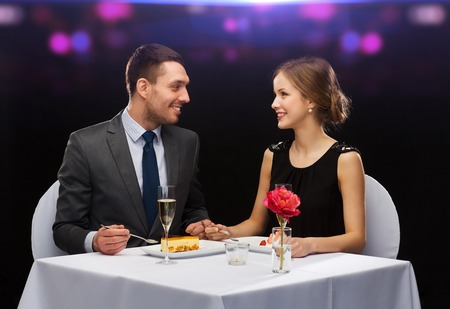 restaurant, couple and holiday concept - smiling couple eating dessert at restaurant photo