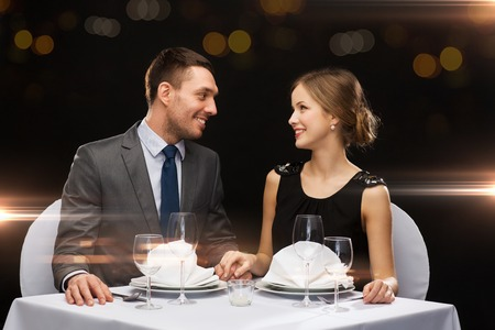 restaurant, couple and holiday concept - smiling couple looking at each other at restaurant photo