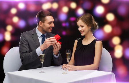 restaurant, couple and holiday concept - excited young woman looking at boyfriend with gift box at restaurant photo