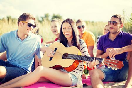 夏、休日、休暇、音楽、幸せな人々 のコンセプト - ビーチで楽しいギターとの友人のグループ