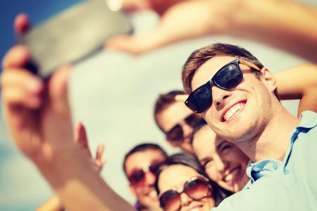 riendo: verano, vacaciones, vacaciones y concepto de la felicidad - grupo de amigos que toman el cuadro con el tel�fono inteligente