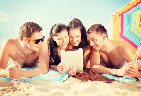 summer, holidays, vacation, technology and happy people concept - group of smiling people with tablet pc under umbrella on the beach photo