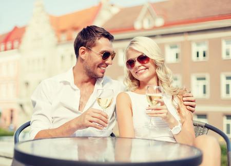 bebiendo vino: vacaciones de verano y el concepto de citas - sonriente, pareja con gafas de sol bebiendo vino en la cafetería