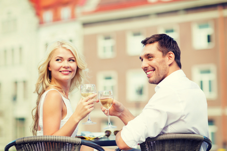 summer holidays and dating concept - smiling couple drinking wine in cafe in the city photo