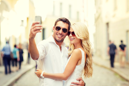 self portrait: summer holidays, technology, love, relationship and dating concept - smiling couple taking picture with smartphone in the city