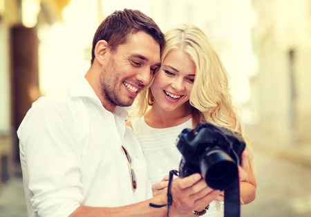 summer holidays and dating concept - smiling couple with photo camera in the city photo