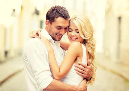 dating: summer holidays, love, travel, tourism, relationship and dating concept - romantic happy couple hugging in the street
