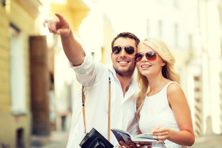 summer holidays, dating, city break and tourism concept - couple with camera and travellers guide photo