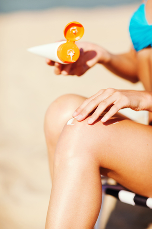 summer holidays and vacation - girl putting sun protection cream on the beach chair photo