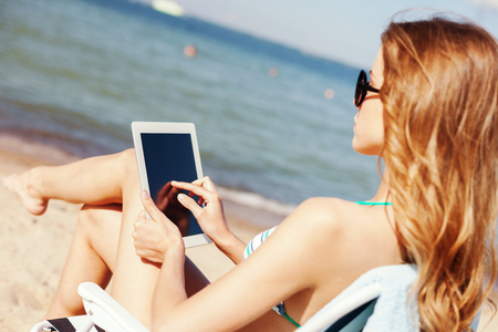 summer holidays, vacation, technology and internet - girl looking at tablet pc on the beach chair photo