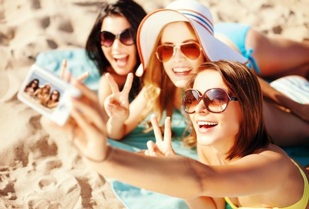 sunbathing: summer holidays, vacation and beach concept - girls taking self photo on the beach