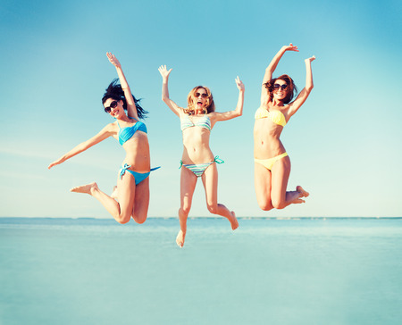 summer holidays and vacation - girls jumping on the beach photo