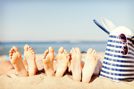 hats and summer concept - three women lying on the beach with straw hat, sunglasses and bag photo