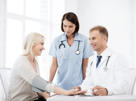 healthcare and medical concept - doctor and nurse with patient measuring blood pressure Stock Photo