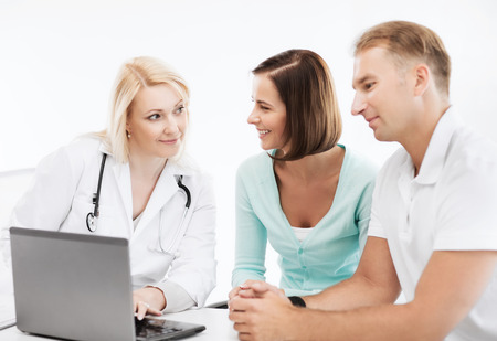 healthcare, medical and technology - doctor with patients looking at laptop photo