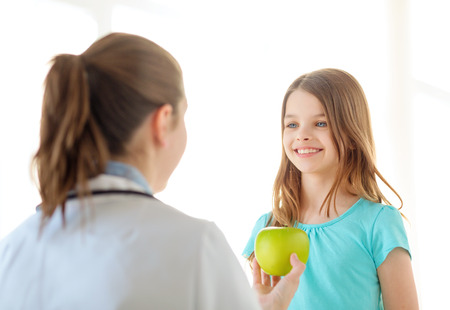 healthcare, child and medicine concept - female doctor giving an apple to smiling little girl photo