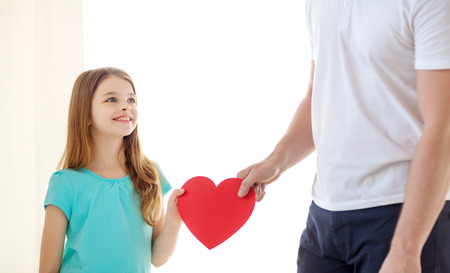 family child, health, charity and love concept - smiling little girl and father holding red heart photo