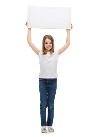 advertisement, art, children, happiness and painting concept - smiling little child in white blank t-shirt holding blank white board photo
