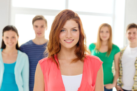 education and school concept - group of smiling students with teenage girl in front photo