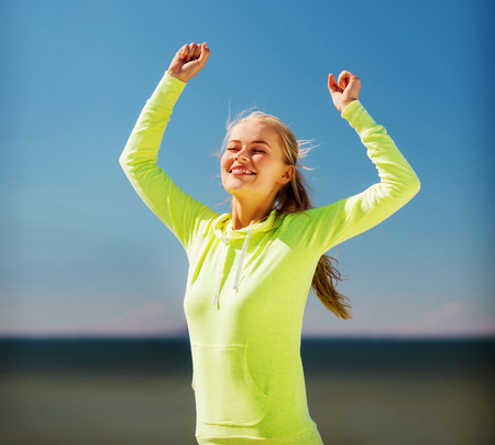 sport and lifestyle concept - woman runner celebrating victory photo